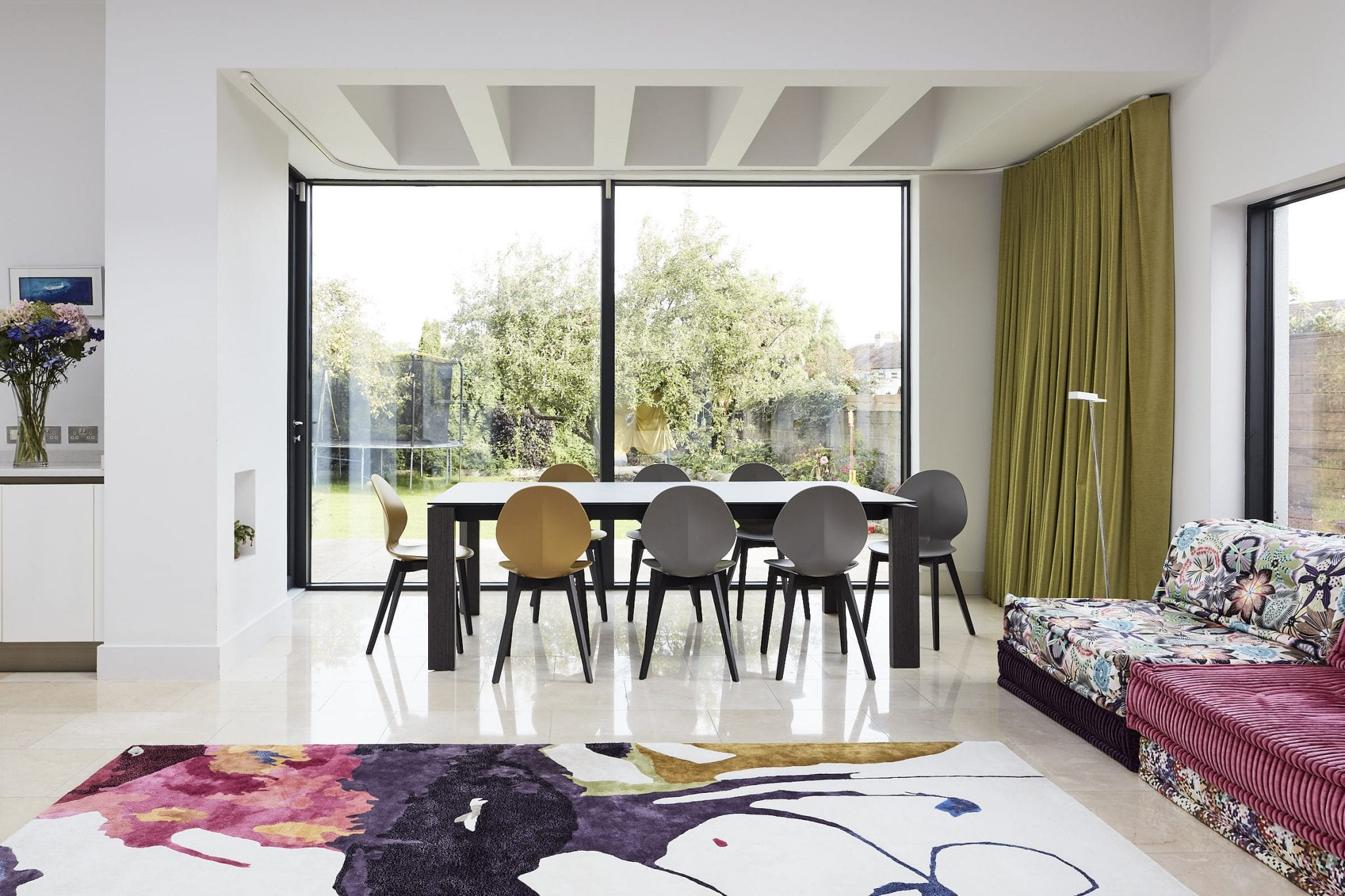Open plan living room,rug,chairs,couch,curtains,artwork