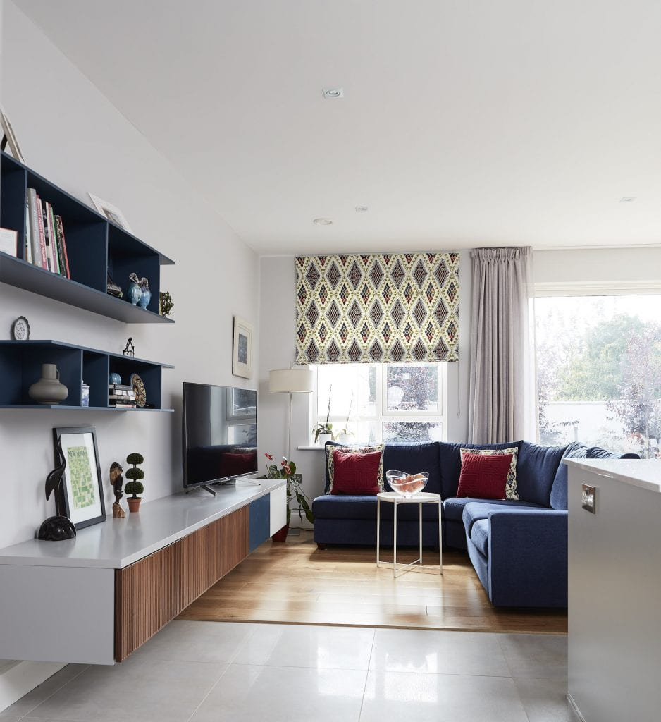 Living area / TV area in the kitchen. Wall mounted units, corner suite, sheer curtains, roman blinds all complete the look for this Dublin 3 interior design project